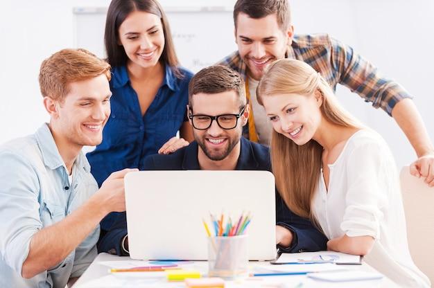 Brainstorming. gruppe fröhlicher geschäftsleute in eleganter freizeitkleidung, die zusammen den laptop betrachten und lächeln