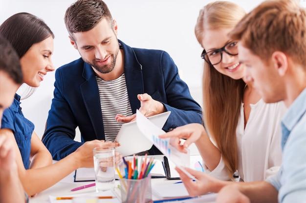 Brainstorming. gruppe fröhlicher geschäftsleute in eleganter freizeitkleidung, die zusammenarbeiten, während sie am tisch sitzen