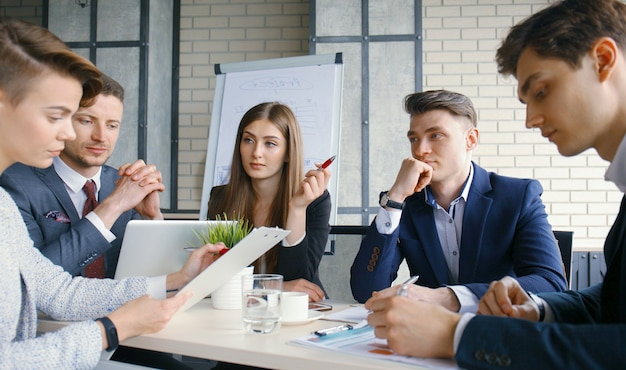 Brainstorming. gruppe geschäftsleute, die zusammen den laptop betrachten.