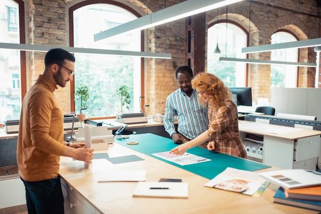 Brainstorming haben. rothaarige, schöne innenarchitektin, die sich ihren kollegen beim brainstorming anschließt