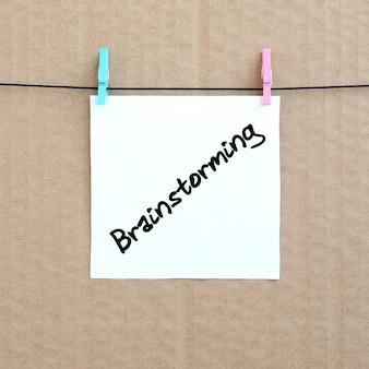 Brainstorming. hinweis steht auf einem weißen aufkleber, der mit einer wäscheklammer hängt