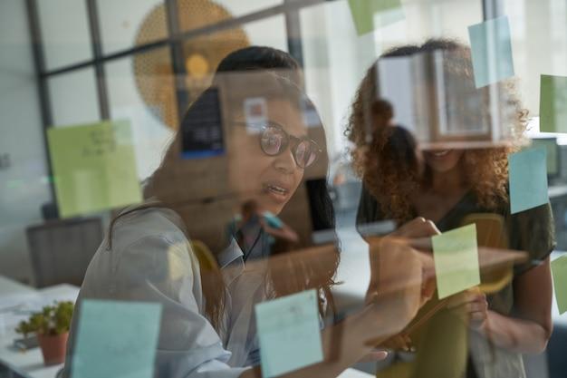 Brainstorming junge gemischtrassige frau mit brille, die etwas auf haftnotizen auf einem glas schreibt