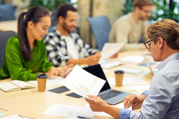Brainstorming-meeting-gruppe gemischtrassiger menschen, die im modernen coworking space am schreibtisch sitzen