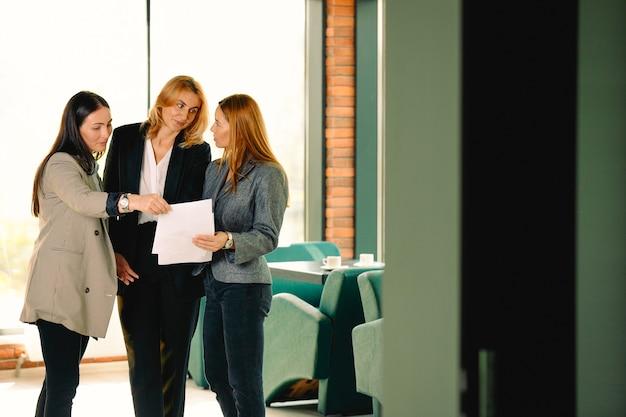 Brainstorming mit geschäftskollegen. erfolg im teamjob. junge manager beim treffen mit einem neuen startup-projekt in einem modernen büro. dokument, pläne analysieren. papiere in händen halten.