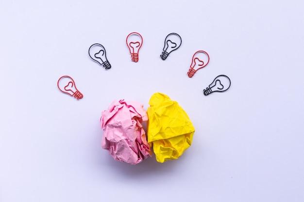 Brainstrom konzept, mit zerknitterten papieren und glühbirne büroklammer