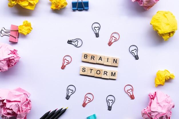 Brainstrom-konzept, wort auf dem holzklotz umgeben durch zerknitterte papiere und papierklammer der glühlampe