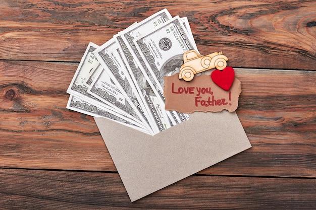 Brandmalerei-auto in der nähe von geld. liebe dich vater grußkarte. machen sie ein besonderes geschenk für papa.