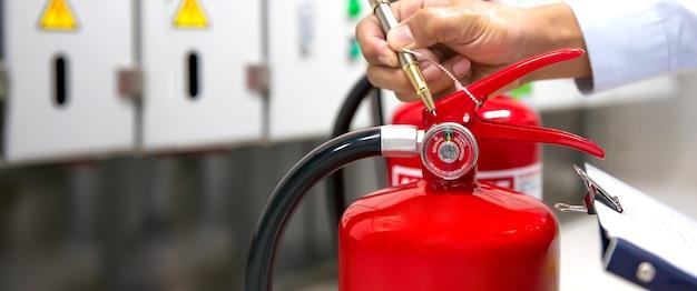 Brandschutztechnik, die den füllstand des manometers des feuerlöschers überprüft.