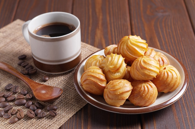 Brandteigkuchen und eine tasse kaffee auf einer leinenserviette