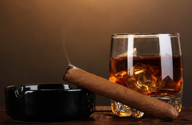 Brandyglas mit eis und zigarre auf holztisch auf brauner oberfläche