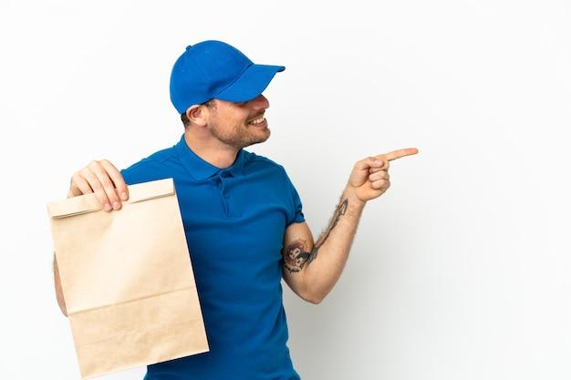 Brasilianer, der eine tüte essen zum mitnehmen einzeln auf weißem hintergrund nimmt, mit dem finger zur seite zeigt und ein produkt präsentiert
