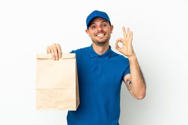 Brasilianer, der eine tüte essen zum mitnehmen isoliert auf weißem hintergrund mit einem ok-zeichen mit den fingern nimmt