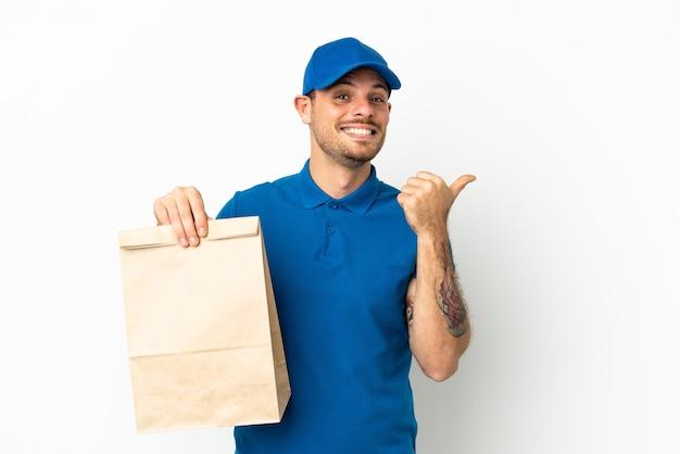 Brasilianer, der eine tüte essen zum mitnehmen isoliert auf weißem hintergrund nimmt und auf die seite zeigt, um ein produkt zu präsentieren?