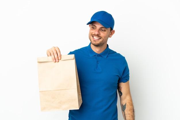 Brasilianer, der eine tüte essen zum mitnehmen nimmt, isoliert auf weißem hintergrund, der zur seite schaut und lächelt