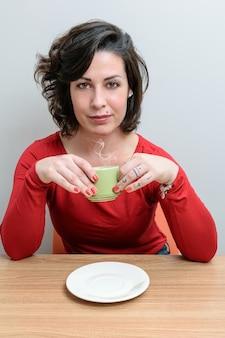 Brasilianerin, mit ernster miene, mit einer tasse kaffee und vor der kamera.