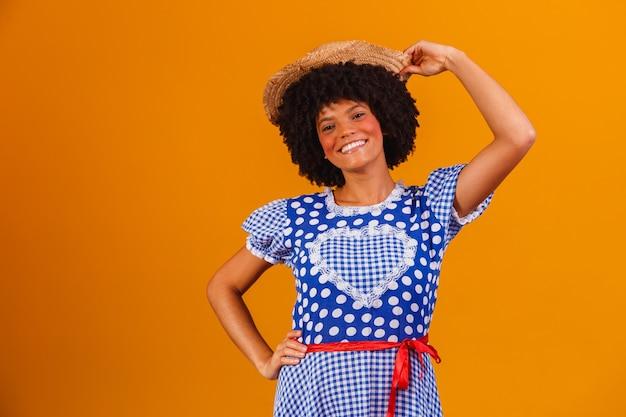 Brasilianische afrofrau, die typische kleidung für die festa junina auf gelb trägt