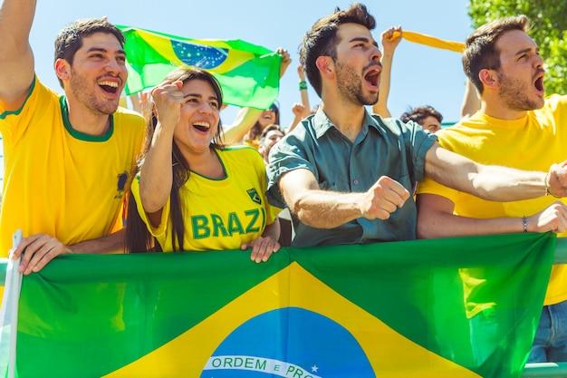 Brasilianische anhänger, die am stadion mit flaggen feiern