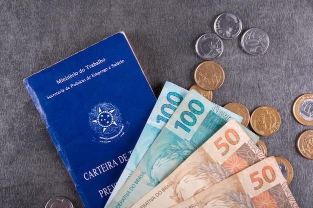 Brasilianische arbeitskarte mit echten scheinen und münzen.