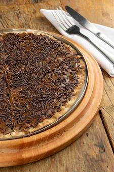 Brasilianische brigadeiro-pizza mit gemahlener schokolade, gabel und messer über holztisch
