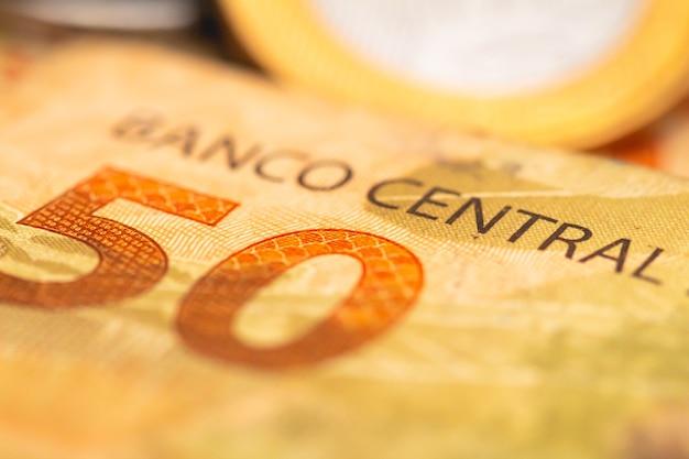 Brasilianische echte banknote von 50 reais in der makrofotografie mit einer münze im hintergrund