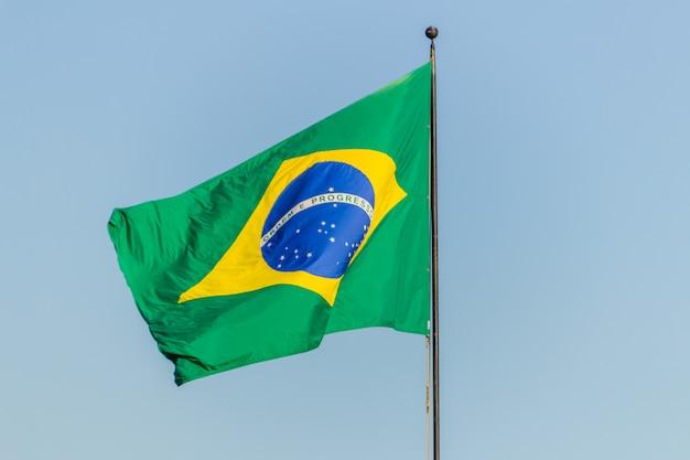 Brasilianische flagge, die mit blauem himmel fliegt