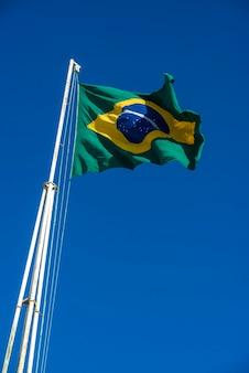 Brasilianische flagge gehisst mit blauem himmel