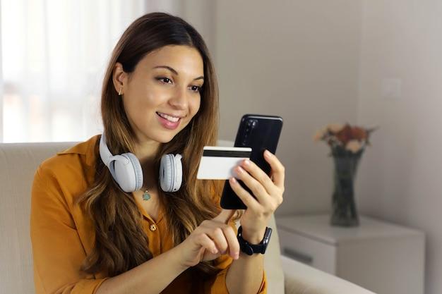 Brasilianische frau, die kreditkartennummer auf mobiltelefon für online-einkäufe zu hause eingibt