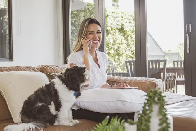 Brasilianische frau, die von zu hause mit ihrem haustierhund arbeitet