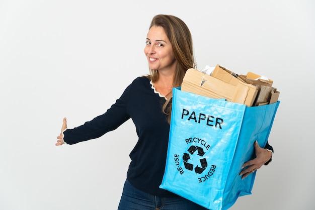 Brasilianische frau mittleren alters, die einen recyclingbeutel voll papier hält, um isoliert zu recyceln
