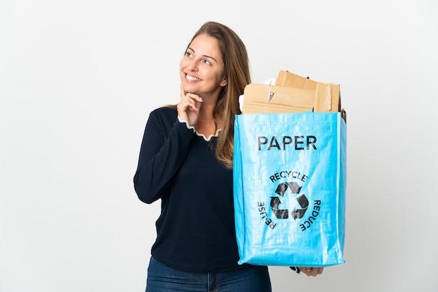 Brasilianische frau mittleren alters, die einen recyclingbeutel voll papier hält, um über isolierte wand zu recyceln, die eine idee denkt, während sie nach oben schaut
