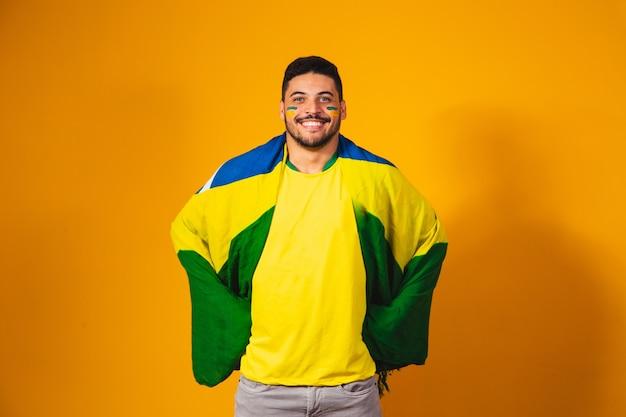 Brasilianische fußballfangefühle: feiernd, aufgeregt, glücklich. anhänger der brasilianischen fußballnationalmannschaft jubelt.