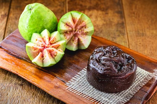 Brasilianische guavenmarmelade, marmelade oder guavenpaste genannt, mit früchten im hintergrund