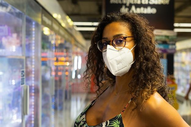 Brasilianische junge frau, die im supermarkt mit maske einkauft. neues normalitätskonzept.