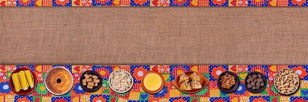 Brasilianische juni-party. typische speisen des juni-festivals. hominy, gekochter mais, maiskuchen, popcorn, brokkoli, paçoca, genipapo und erdnüsse. draufsicht mit kopienraum.