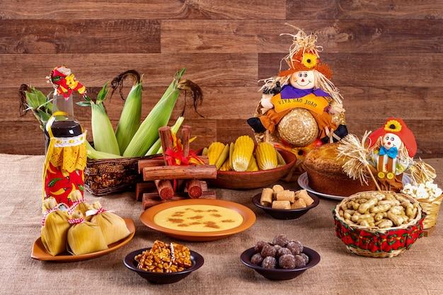 Brasilianische juni-party. typische speisen des juni-festivals. hominy, gekochter mais, maiskuchen, popcorn, brokkoli, paçoca, genipapo und erdnüsse. es steht geschrieben: viva sao joao auf portugiesisch.