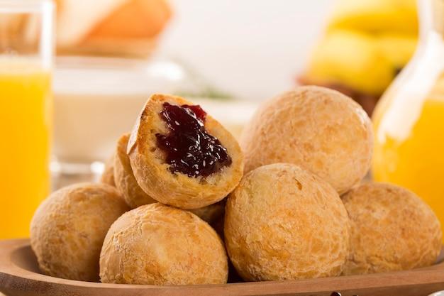 Brasilianische käsebrötchen. tischcafé am morgen mit käsebrot und obst.