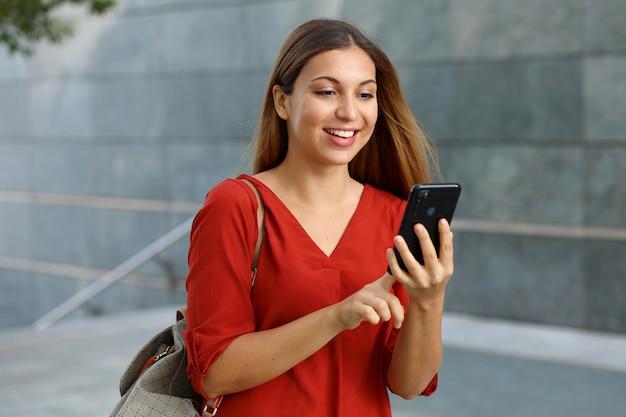 Brasilianische kaukasische geschäftsfrau, die einkaufs-online-app auf smartphone in der straße verwendet