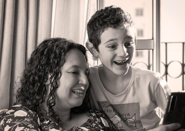 Brasilianische mutter und sohn lächeln und sehen das smartphone zusammen