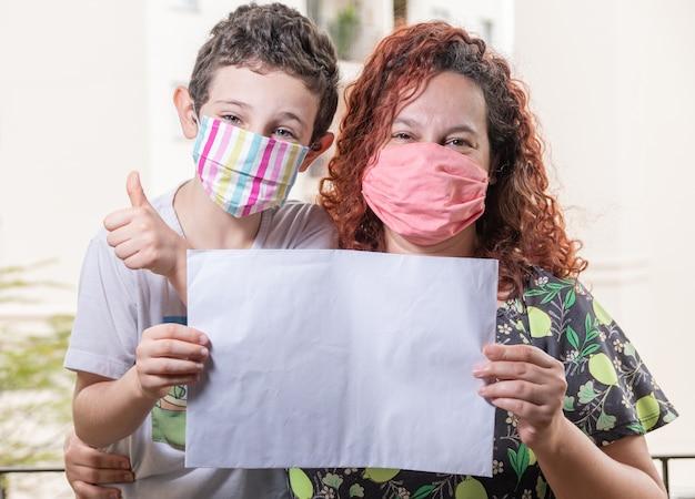 Brasilianische mutter und sohn tragen maske, die leeres papier hält