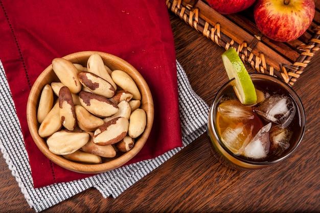 Brasilianische nüsse auf einem holztisch mit äpfeln und eistee im hintergrund.