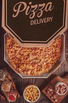 Brasilianische pizza mit mozzarella, mais, speck und oregano in einer lieferbox (pizza de milho com bacon) - draufsicht.