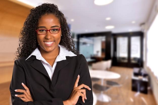 Brasilianische schwarze geschäftsfrau, die kamera auf unscharfen büroräumen betrachtet. speicherplatz kopieren.