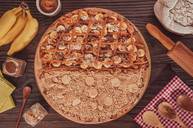 Brasilianische süße pizza halb banane, dulce de leche und zimt und halb pizza erdnussbonbons. (pizza meio a meio) - ansicht von oben.