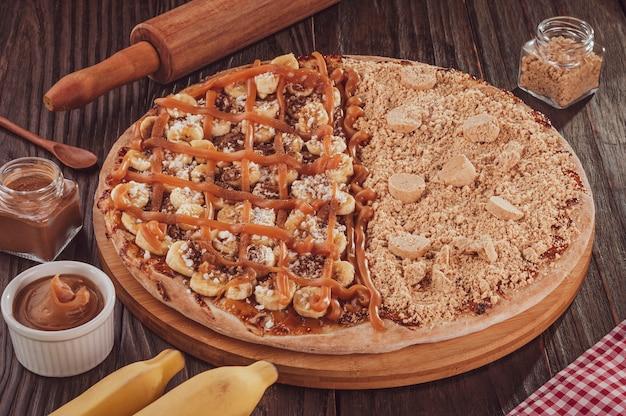 Brasilianische süße pizza halb banane, dulce de leche und zimt und halb pizza erdnussbonbons. (pizza meio a meio)