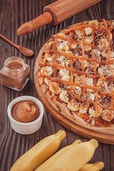Brasilianische süße pizza mit banane, dulce de leche und zimt.