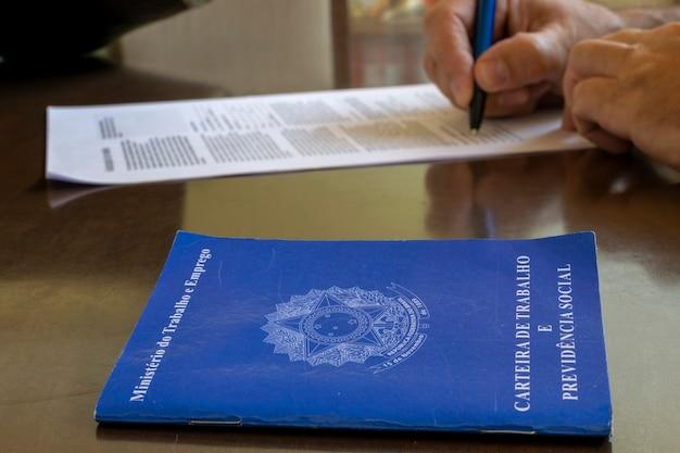 Brasilianischer arbeitsausweis und im hintergrund die unterzeichnung eines arbeitsvertrags. konzept für die einstellung von mitarbeitern.