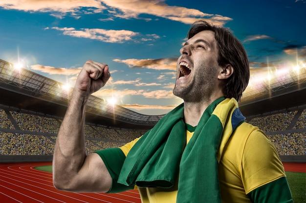 Brasilianischer athlet gewinnt eine goldene medaille in einem leichtathletikstadion.