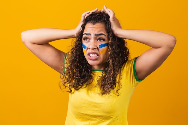 Brasilianischer fan aufgeregt und nervös wegen des spiels auf gelbem hintergrund