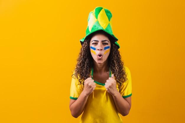 Brasilianischer fan. brasilianischer fan, der fußball- oder fußballspiel auf gelbem hintergrund feiert. farben brasiliens.