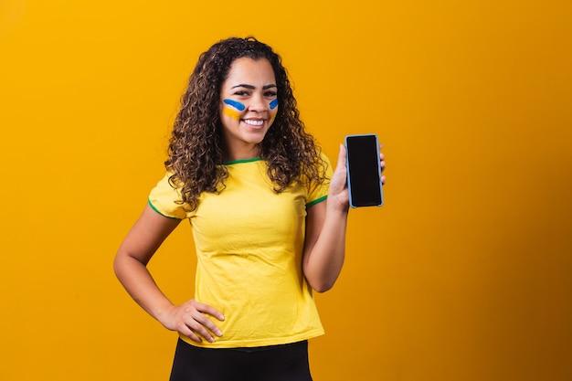 Brasilianischer fan, der ein smartphone mit kopienraum hält